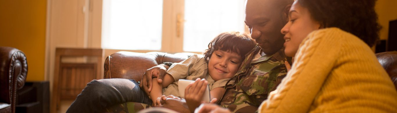Armed forces family of three sitting on sofa. Father wearing camouflage uniform.